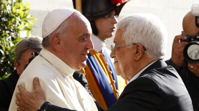 Pope Francis welcomes Palestinian President Mahmoud Abbas, right, as he arrives at the Vatican, Sunday, June 8, 2014. Pope Francis waded head-first into Mideast peace-making Sunday, welcoming the Israeli and Palestinian presidents to the Vatican for an evening of peace prayers just weeks after the last round of U.S.-sponsored negotiations collapsed. (AP Photo/Riccardo De Luca, Pool)