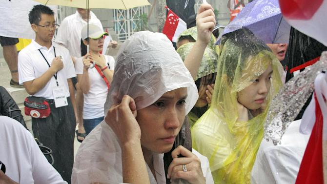 Standing in a downpour, Singaporeans wait for the carriage carrying the coffin of Lee Kuan Yew to pass during the funeral procession, Sunday, March 29, 2015, at City Hall in Singapore. Tens of thousands of Singaporeans undeterred by heavy rains lined a 15 kilometer (9 mile) route through the Southeast Asian city-state to witness an elaborate funeral procession Sunday for longtime leader Lee Kuan Yew, who died Monday at 91. (AP Photo/Jeanette Tan)