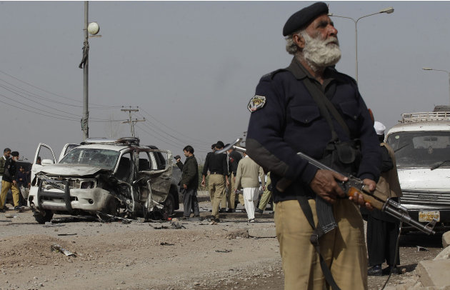 A Pakistani police officer stands guard at the site of a suicide attack in Peshawar, Pakistan on Thursday, March 15, 2012. The attack killed a senior police officer and wounded others. (AP Photo/Moham