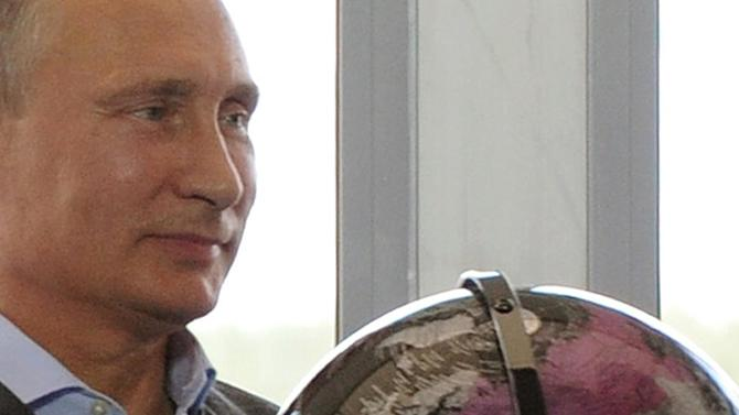 FILE - In this Aug. 29, 2014, file photo, Russian President Vladimir Putin holds a terrestrial globe, with Russian territory colored pink, seemingly including Crimea, presented to him as a gift during his meeting with participants in the youth educational forum at the Seliger youth camp near Lake Seliger, Russia. As world leaders gather at the U.N., during the week of Sept. 22, 2014, the U.S. and its European allies are consumed by efforts to blunt the savage advance of the Islamic State group, to end the raging Ebola epidemic and to make progress in nuclear negotiations with Iran. That's likely just fine with Putin, since these issues distract from Russia's presence in neighboring Ukraine. (AP Photo/RIA-Novosti, Presidential Press Service, Mikhail Klimentyev, Pool, File)