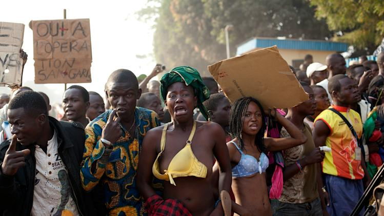 Women bare their chests in a traditional sign of placing a curse, after at least two people were injured by passing Chadian troops, during a protest outside Mpoko Airport in Bangui, Central African Republic, Monday, Dec. 23, 2013. Hundreds of demonstrators gathered at the entrance to the airport Monday morning carrying signs protesting Chadian forces and expressing support for French troops and other regional African forces. At least two people were wounded as pickups of Chadian soldiers sped through the gathered crowd firing off several rounds. (AP Photo/Rebecca Blackwell)