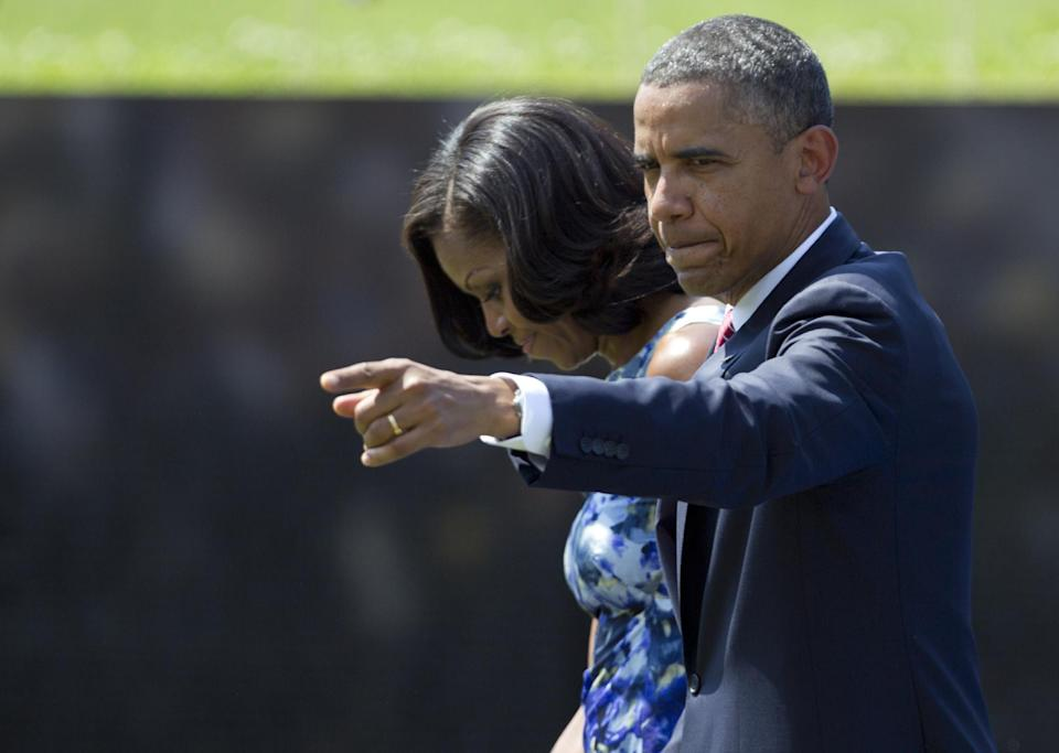 President Barack Obama points to the audience as he and first lady Michelle Obama leave the stage after a Memorial Day ceremony at the Vietnam Veterans Memorial Wall to commemorate the 50th anniversary of the Vietnam War, Monday, May 28, 2012, in Washington. (AP Photo/Carolyn Kaster)
