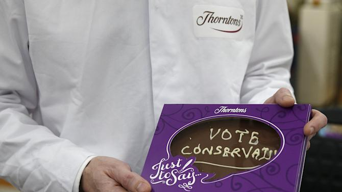 Britain's Chancellor of the Exchequer Osborne holds up a slab of chocolate at the Thorntons chocolate factory in Alfreton