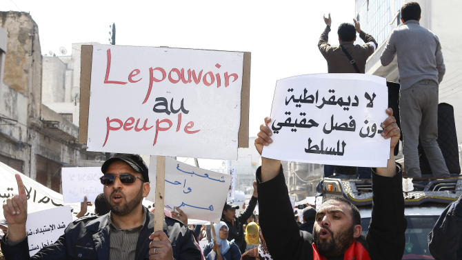 "FILE - In this Sunday, March 20, 2011 file photo, demonstrators with various signs, including at right, ""Separation of Powers,"" and at left, ""Power to People,"" march while denouncing corruption, demanding better civil rights and a new constitution, in Casablanca, Morocco. In an interview with The Associated Press, Fathallah Arsalane, political leader of Al Adl wal Ihsan, or the Justice and Charity movement, warned that Morocco is at serious risk of a popular revolt if the state doesn't recognize the demands of the Arab Spring and implement real democratic reforms. (AP Photo/Abdeljalil Bounhar, File)"