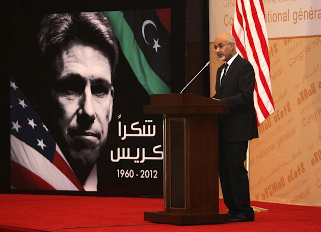 "Libyan President Mohammed el-Megarif speaks during a memorial service in Tripoli, Libya, Thursday, Sept. 20, 2012, for U.S. Ambassador to Libya, Chris Stevens, and three consulate staff killed in Benghazi on Sept. 11. The deputy U.S. secretary of state has met senior Libyan officials in Tripoli and attended a memorial service for the American ambassador and three consulate staffers killed in an attack last week. William Burns is the most senior US official to visit Libya in the aftermath of the Sept. 11 attack on the consulate in Benghazi and comes as Washington is still working to piece together how its top diplomat there, Ambassador Chris Stevens, was killed. Arabic on the poster reads, ""thank you, Chris."" (AP Photo/Abdel Magid al-Fergany)"