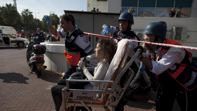 Israeli rescue workers and paramedics carry a wounded person from the site of a bombing in Tel Aviv, Israel, Wednesday, Nov. 21, 2012. A bomb ripped through an Israeli bus near the nation's military headquarters in Tel Aviv on Wednesday, wounding several people, Israeli officials said. The blast came amid a weeklong Israeli offensive against Palestinian militants in Gaza that has killed more than 130 Palestinians. (AP Photo/Oded Balilty)