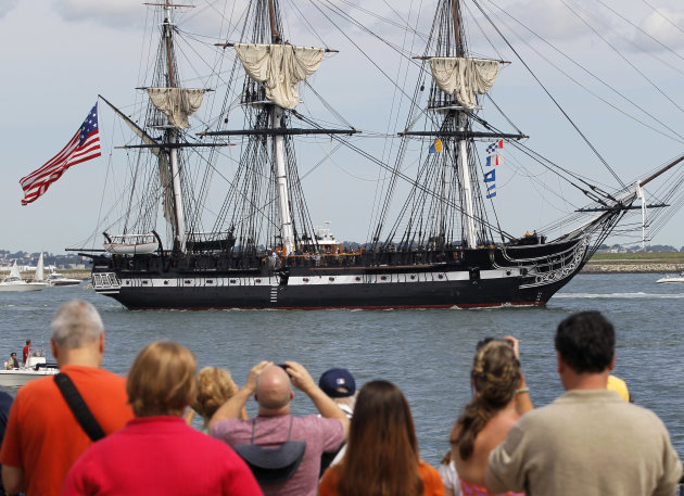 The USS Constitution is escorted by a tugboat in Boston Harbor as a crowd looks on from the shore in Boston, Sunday, Aug. 19, 2012. The USS Constitution, the U.S. Navy's oldest commissioned war ship, sailed under her own power during the event Sunday for the first time since 1997. The sail was held to commemorate the 200th anniversary of the ship's victory over HMS Guerriere in the War of 1812. (AP Photo/Steven Senne)
