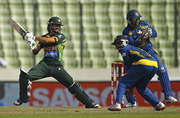 Pakistan's Fawad Alam, left, plays a shot in front of Sri Lankan wicketkeeper Kumar Sangakkara, right, and a teammate during their Asia Cup final cricket match in Dhaka, Bangladesh, Saturday, Marc