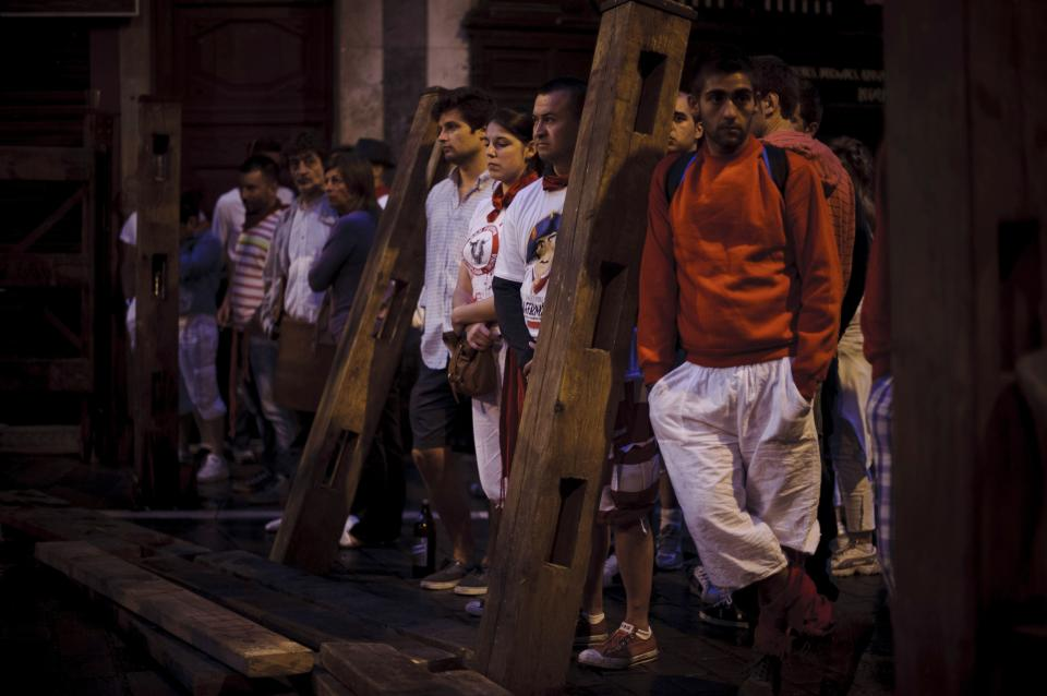 Revelers wait for the running of the bulls of the San Fermin festival, in Pamplona, Spain, Monday, July 9, 2012. (AP Photo/Daniel Ochoa de Olza)