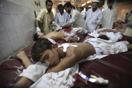 Pakistani doctors treat youths injured in an attack , at a local hospital in Peshawar, Pakistan on Tuesday, Sept 13, 2011. Gunmen attacked a school van in northwestern Pakistan killing three children, the driver and police said. (AP Photo/Mohammad Sajjad)