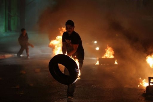A Palestinian youth prepares to throw a burning tyre during a protest against the high cost of living at Al-Amari refugee camp near the West Bank city of Ramallah