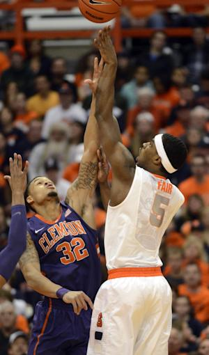 CORRECTS TO CLEMSON'S K.J. MCDANIELS NOT JARON BLOSSOMGAME - Syracuse's C.J. Fair, right, shoots over Clemson's K.J. McDaniels during the first half of an NCAA college basketball game in Syracuse, N.Y., Sunday, Feb. 9, 2014. (AP Photo/Kevin Rivoli)