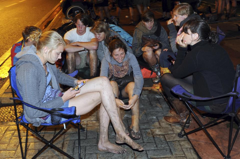 Visitors wait for transport to leave after a storm swept through an open air music festival near Hasselt, about 50 miles (80 kilometers) east of Brussels, Belgium, Thursday, Aug. 18, 2011. The storm killed at least three people and injured over 70 others, an official said. (AP Photo/ Ermindo Armino)