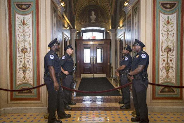 U.S. Capitol Police officers stand guard as doors are locked down inside the Capitol Building during the shooting at the Washington Navy Yard, Monday, Sept. 16, 2013, in Washington. (AP Photo/J. Scott