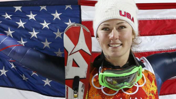 First-placed Shiffrin of the U.S. poses with a U.S. flag after the flower ceremony for the women's alpine skiing slalom event at the 2014 Sochi Winter Olympics at the Rosa Khutor Alpine Centre