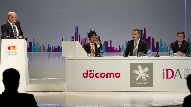 IMAGE DISTRIBUTED FOR MASTERCARD - From left, Matthew Barr (MasterCard), Takashi Komoro (NTT DOCOMO), Edward Hyde (Telecom NZ) and Tan Eng Pheng (IDA Singapore) at the MasterCard Mobile Payments Symposium discussing the future of mobile payment in the Asia-Pacific region at the Mobile World Congress on Tuesday, Feb. 26, 2013 in Barcelona. (Marcel-li Saenz Martinez/AP Images for MasterCard)