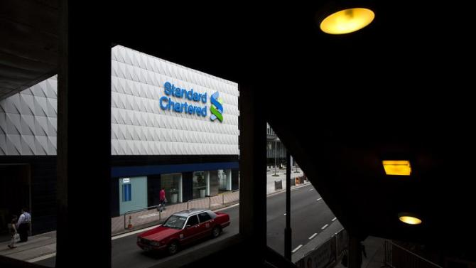 Taxi drives past Standard Chartered's main branch in Hong Kong