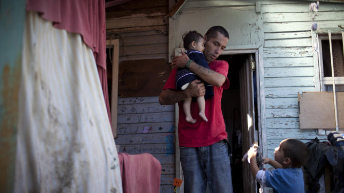 "Ricardo Gonzalez holds her 8-month old daughter Keyla as his son Antonio, right, 3, talks to him at their home in the San Pablo shanty town in Santiago, Chile, Wednesday, Jan. 23, 2013. European, Latin American and Caribbean leaders gathering for this weekend's economic summit will likely see only one side of Chile _ the polished, upscale country where tourists and investors stay in five-star hotels in a sparklingly clean financial district nicknamed ""Sanhattan,"" well away from Santiago's slums. (AP Photo/Victor R. Caivano)"