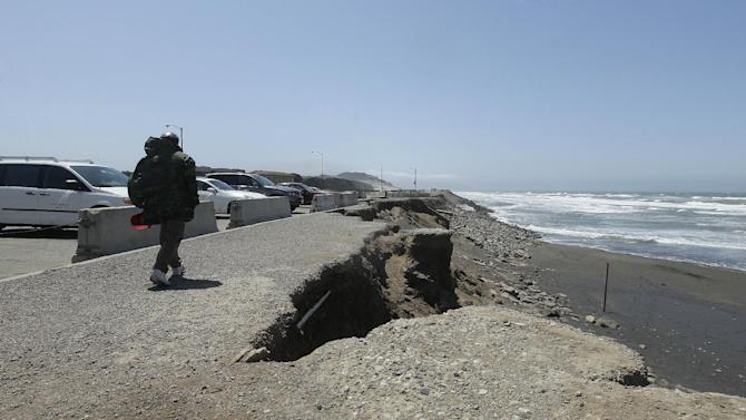 In this photo from Thursday, May 24, 2012, a man walks in the parking lot at Ocean Beach in San Francisco. In San Francisco, officials are mulling a significant retreat on its western flank, where the Great Highway is under assault from the Pacific Ocean. Right now, a beach parking lot that abuts the highway is crumbing into the sea just across the highway from the San Francisco Zoo. (AP Photo/Jeff Chiu)