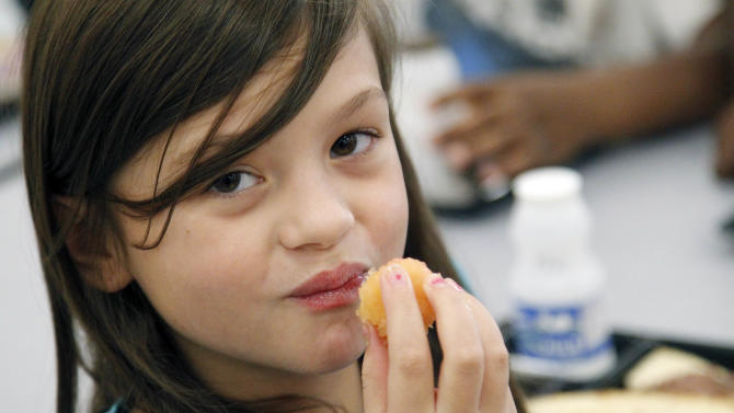 Nutrition is not on the mind of Eastside Elementary School fourth grader Grace Bethany when she chose her school lunch Wednesday, Sept. 12, 2012, in Clinton, Miss. What mattered, was the tartness of the plum that accompanied the flat bread roast beef sandwich. The leaner, greener school lunches served under new federal standards are getting mixed grades from students.  (AP Photo/Rogelio V. Solis)