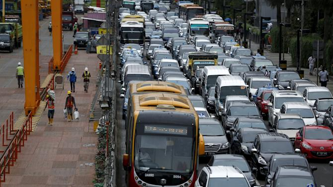 Rush hour traffic is seen next to a construction site for a light railway in Jakarta