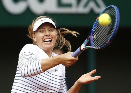 Maria Sharapova of Russia plays a shot to Kaia Kanepi of Estonia during their women's singles match at the French Open tennis tournament at the Roland Garros stadium in Paris