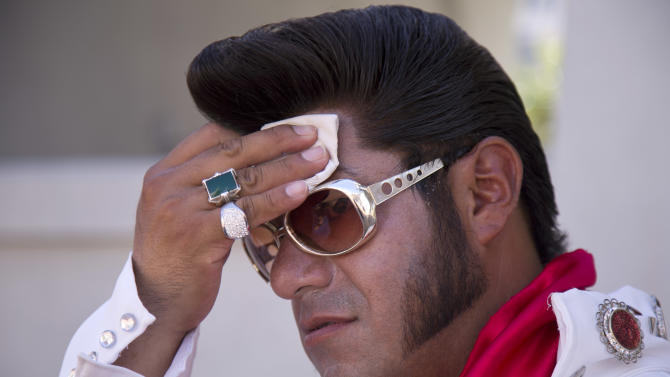 """Elvis impersonator Cristian Morales wipes sweat from his brow while standing out on The Strip posing for photos with tourists, Thursday, June 27, 2013 in Las Vegas. Morales preferred to stand out in the 112 degree heat of the day instead of working the cooler evening hours saying """"We'd much rather fight with the sun than fight with the drunk people."""" A high pressure system parking over the West is expected to bring temperatures this weekend and into next week that are extreme even for a region used to baking during the summer. (AP Photo/Julie Jacobson)"""