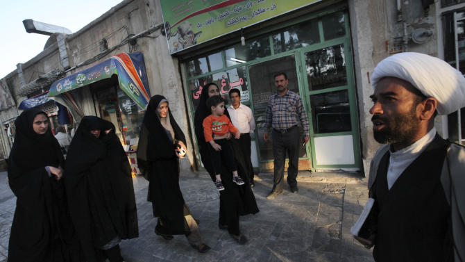 In this picture taken on Sunday, May 4, 2013, an Iranian cleric, right, and women, left, walk in a sidewalk at the eastern city of Birjand, Iran. When struggling families in the eastern Iranian city of Birjand take measure of Mahmoud Ahmadinejad's presidency in its waning weeks, it's not about his browbeating oratory against the West or his battles with Iran's ruling clerics. Instead, it's the rows of simple two-story homes on the city's outskirts that sharply improved their lives. (AP Photo/Vahid Salemi)