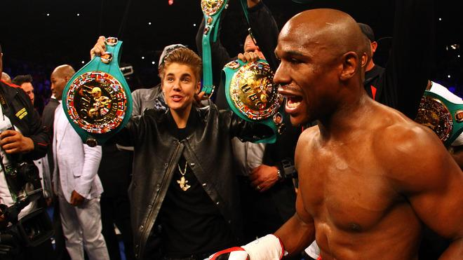 Pop star Justin Bieber holds up Floyd Mayweather's belts before his fight against Miguel Cotto.