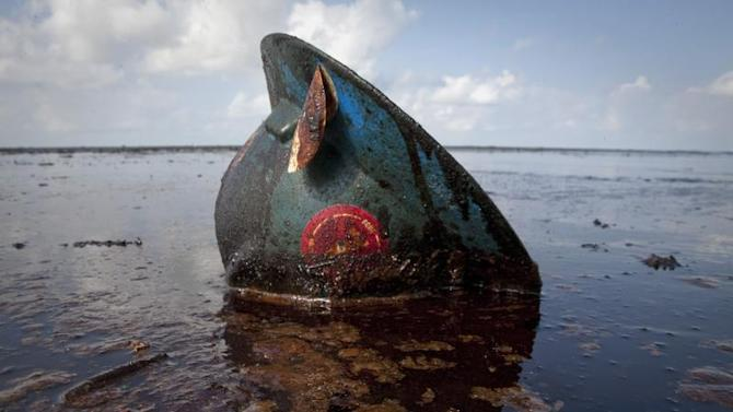 A hard hat from an oil worker lies in oil from the Deepwater Horizon oil spill on East Grand Terre Island, Louisiana