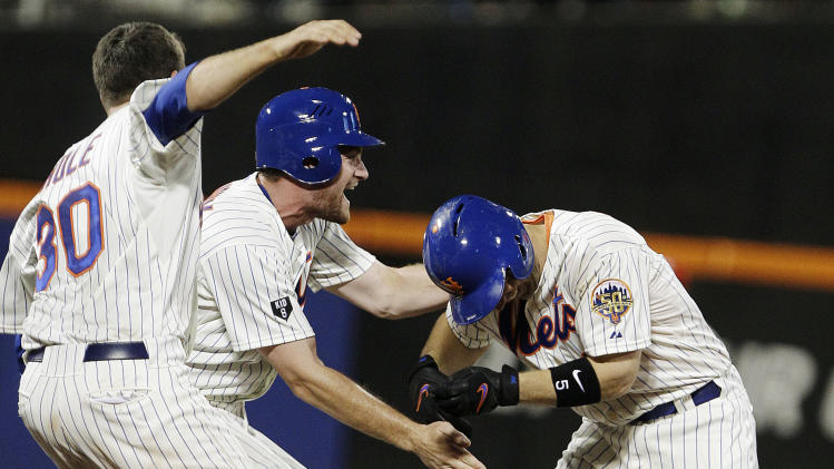 New York Mets' Josh Thole, left, and Daniel Murphy, center, celebrate with David Wright after Wright drove in the game-winning run during the ninth inning of a baseball game against the Philadelphia Phillies, Thursday, July 5, 2012, in New York. The Mets won 6-5. (AP Photo/Frank Franklin II)