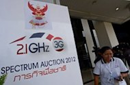 A Thai official walks past a sign for the 3G Spectrum Auction at the National Broadcasting and Telecommunications Commission (NBTC) in Bangkok on October 16. Thailand's finance ministry on Friday called for a corruption investigation into the auction because of fears of collusion