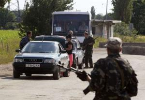Pro-Russian separatists inspect vehicles at a road …