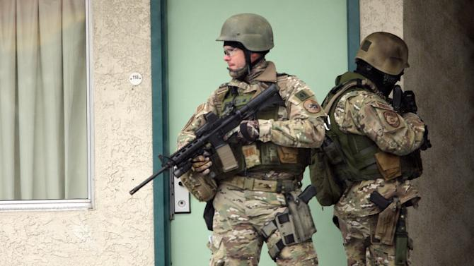"Unified Police Department SWAT officers look for a person of interest at a local Midvale, Utah motel in connection with a multiple victim shooting, Tuesday, Feb. 12, 2013. Three people were shot to death and one was critically wounded at a known drug house in suburban Salt Lake City, causing temporary lockdowns at several area schools as police looked for two men who may have been involved. Investigators said a person inside the house reported the shooting in Midvale at about 8 a.m. Unified Police Department Lt. Justin Hoyal said a search warrant had been served at the house in recent weeks for drug activity. ""It was a known narcotics house,"" he said. (AP Photo/The Deseret News, Jeffrey D. Allred)  SALT LAKE TRIBUNE OUT;  MAGS OUT"