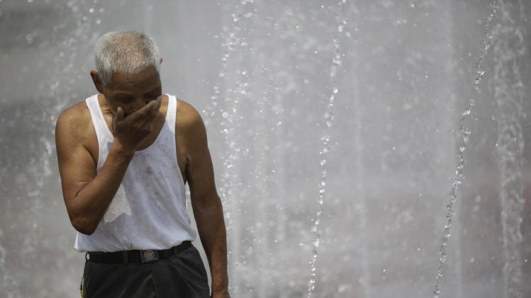 A man cools off in a fountain at a park in Shanghai, China, Thursday, Aug. 1, 2013. Hot weather has set in with temperatures rising up to 40 degrees Celsius (104 degrees Fahrenheit) in Shanghai. (AP Photo/Eugene Hoshiko)