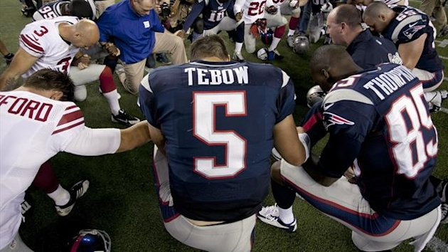 New England Patriots quarterback Tim Tebow prays with his teammates and members of the New York Giants after their NFL preseason game in Foxborough, Massachusetts, August 29, 2013 (Reuters)