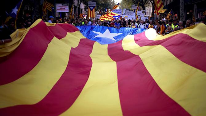 "FILE- In this Sept. 11, 2012 file photo, demonstrators carry a Catalan flag during a protest rally demanding independence for Catalonia in Barcelona, Spain.  More than ever, FC Barcelona, known affectionately as Barca, lived up to its motto of being ""more than a club"" for this wealthy northeastern region where Spain's economic crisis is fueling separatist sentiment. Barca has been seen as a bastion of Catalan identity dating back to the three decades of dictatorship when Catalans could not openly speak, teach or publish in their native Catalan language. Barcelona writer Manuel Vazquez Montalban famously called the football team ""Catalonia's unarmed symbolic army."" (AP Photo/Emilio Morenatti, File)"