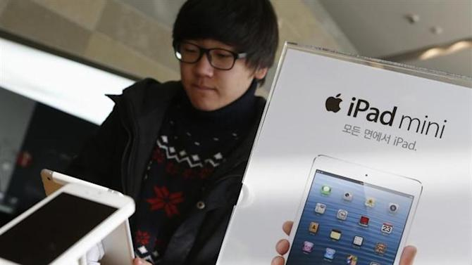 A student tries Apple Inc's iPad mini at an electronics store in central Seoul January 18, 2013. REUTERS/Lee Jae-Won/Files