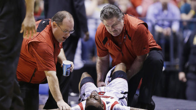Trainers check on Louisville guard Kevin Ware (5) after an injury during the first half of the Midwest Regional final against Duke in the NCAA college basketball tournament, Sunday, March 31, 2013, in Indianapolis. (AP Photo/Michael Conroy)