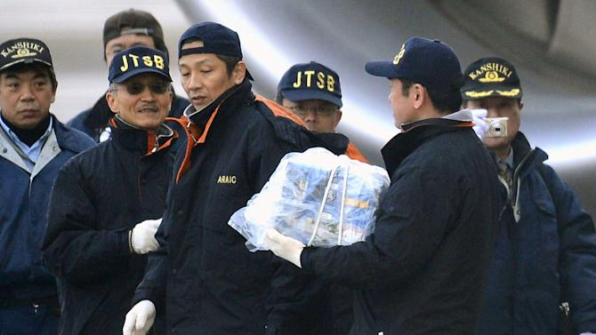 An official carries a main battery that was removed off an electrical room beneath the cockpit of an All Nippon Airways 787 at Takamatsu airport in Takamatsu, western Japan, Thursday, Jan. 17, 2013. The battery forced to make the emergency at the airport was swollen from overheating, a safety official said Thursday, as India and Europe joined the U.S. and Japan in grounding the technologically advanced aircraft because of fire risk. (AP Photo/Kyodo News)  JAPAN OUT, MANDATORY CREDIT, NO LICENSING IN CHINA, HONG KONG, JAPAN, SOUTH KOREA AND FRANCE