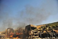 "A picture taken on July 20 shows lorries burning at the Bab al-Hawa border post with Turkey after it was seized by Syrian rebels following fierce battle with Syrian troops in Bab al-Hawa. ""All of our trucks were burned,"" said trader Ali Cengiz, who exports to Saudi Arabia via Syria. ""The rebel fighters destroyed our trucks during the clashes."""