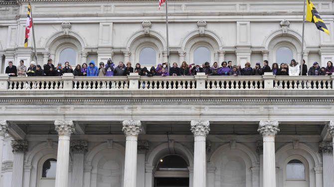 Baltimore Ravens linebacker Ray Lewis, bottom center, holding the Vince Lombardi trophy, speaks to fans at a celebration at City Hall at the start of a Super Bowl victory parade Tuesday, Feb. 5, 2013, in Baltimore. The Ravens defeated the San Francisco 49ers in NFL football's Super Bowl XLVII 34-31 on Sunday. (AP Photo/Gail Burton)