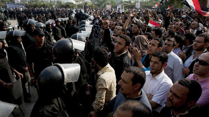 "Supporters of Egyptian President Mohammed Morsi chant slogans as riot police, left, stand guard in front of the entrance of Egypt's top court, in Cairo, Egypt, Sunday, Dec. 2, 2012. Egypt's top court announced on Sunday the suspension of its work indefinitely to protest ""psychological and physical pressures,"" saying its judges could not enter its Nile-side building because of the Islamist president's supporters gathered outside. (AP Photo/Nasser Nasser)"