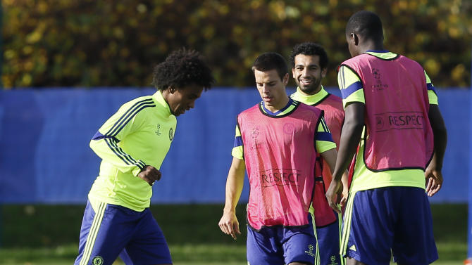 Chelsea's Brazilian player Willian, left, , controls the ball during a training session, at the training ground in Cobham, England, Monday, Oct. 20, 2014. Chelsea will play Maribor in a Champions League Group G soccer match at Stamford Bridge stadium on Tuesday. (AP Photo/Kirsty Wigglesworth)