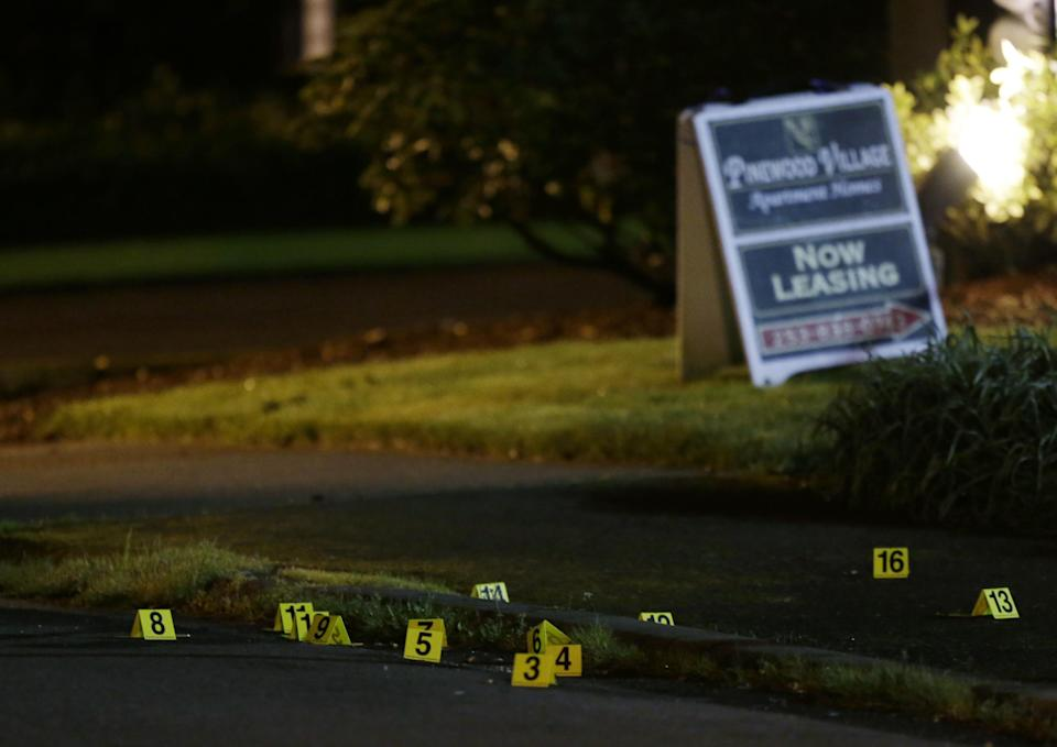 Evidence markers are shown near a leasing sign at the scene of an overnight shooting that left five people dead, Monday, April 22, 2013, at the Pinewood Village apartment complex in Federal Way, Wash. (AP Photo/Ted S. Warren)
