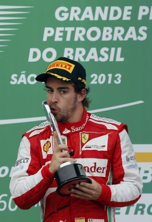 Fernando Alonso of Spain kisses the trophy during podium celebrations after the Brazilian F1 Grand Prix at the Interlagos circuit in Sao Paulo