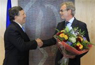 European Commission President Jose Manuel Barroso (L) receives flowers from Atle Leikvoll, Norway's Ambassador to the European Union, at the EC headquarters in Brussels October 12, 2012, after the European Union won the Nobel Peace Prize for its long-term role in uniting the continent, an award seen as morale boost for the bloc as it struggles to resolve its debt crisis. The Norwegian Nobel Committee praised the 27-nation EU for rebuilding after World War Two and for its role in spreading stability to former communist countries after the 1989 fall of the Berlin Wall. REUTERS/Yves Herman