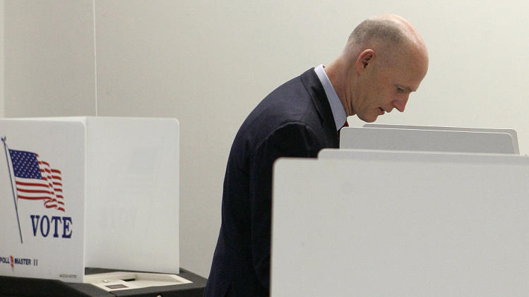 FILE - In this Jan. 31, 2012, file photo Florida Gov. Rick Scott casts his ballot as he votes in the Republican presidential primary in Tallahassee, Fla. The Justice Department is opposing changes in Florida voting procedures and says it wants a trial in the dispute, a move that could impact the state's August primary elections. In court papers filed Friday night, March 2, 2012, Florida officials say they strongly oppose having a trial and noted that the federal court hearing the case in Washington wants sufficient time to issue a decision before the August primaries.  (AP Photo/Steve Cannon, File)