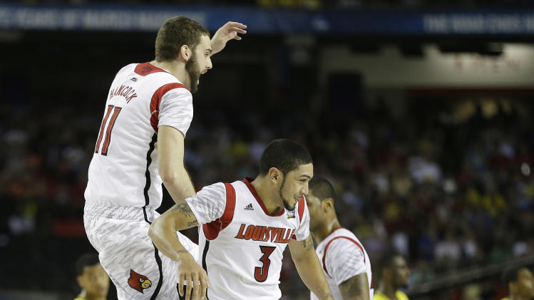 Louisville guard Peyton Siva (3) and Louisville guard/forward Luke Hancock (11) celebrate their teams victory over Michigan during the second half of the NCAA Final Four tournament college basketball championship game Monday, April 8, 2013, in Atlanta. Louisville won 82-76. (AP Photo/Charlie Neibergall)