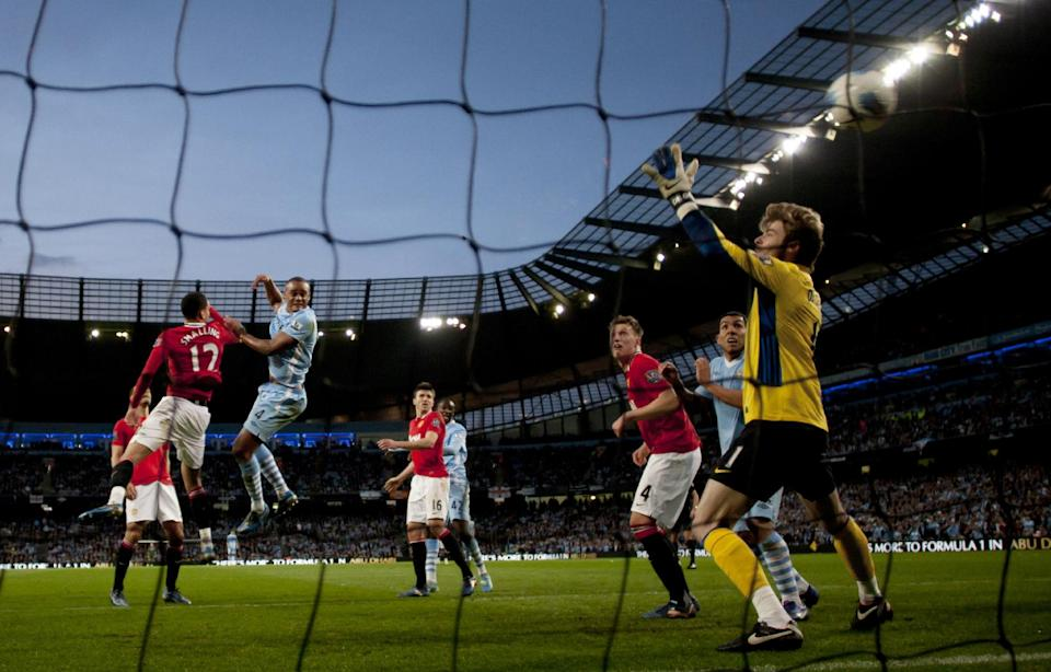 Manchester City's Vincent Kompany, second left, scores against Manchester United during their English Premier League soccer match at The Etihad Stadium, Manchester, England, Monday, April 30, 2012. (AP Photo/Jon Super)